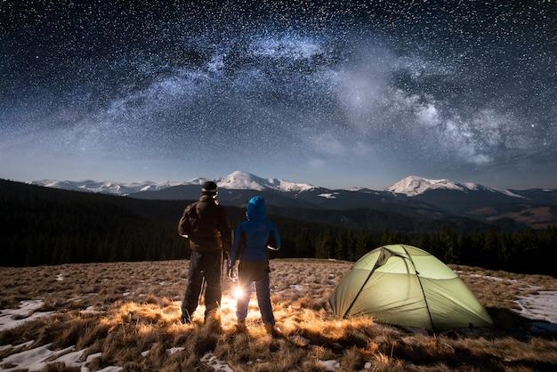 Vista traseira jovem casal turistas descansando no acampamento à noite