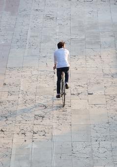 Vista traseira jovem ciclismo na rua