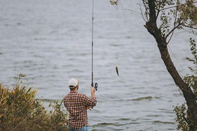 Vista traseira jovem com barba por fazer com uma vara de pescar em camisa xadrez e boné puxa a vara de pescar com peixes capturados no lago da costa perto de arbustos e juncos. estilo de vida, conceito de lazer do pescador.