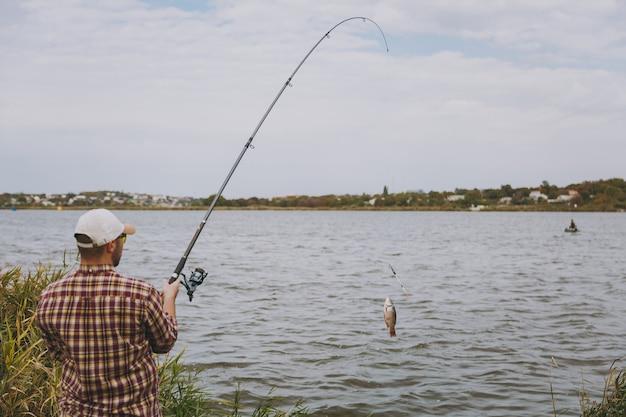 Vista traseira jovem com barba por fazer com vara de pescar em camisa xadrez, boné e óculos de sol puxa uma vara de pescar no lago da costa perto de arbustos e juncos. estilo de vida, recreação, conceito de lazer de pescador