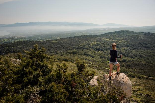 Vista traseira jovem de pé sobre a rocha em shorts com bengalas