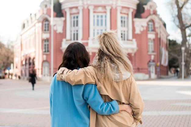 Vista traseira jovens mulheres posando juntos