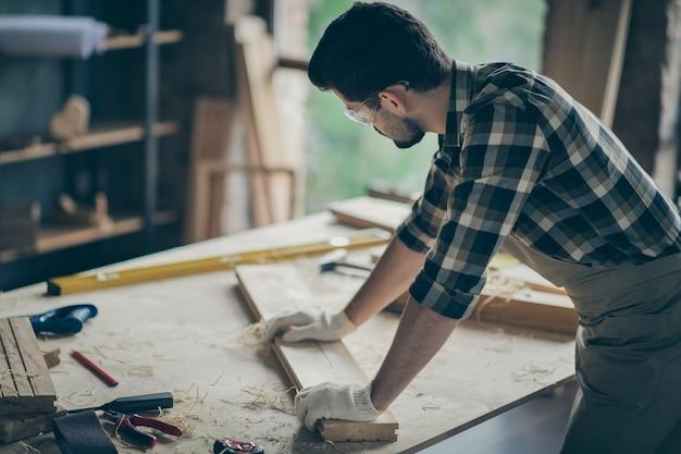 Vista traseira lateral traseira concentrada homem trabalhador trabalhando com plano longo de madeira mobília restaurada verifique alisamento na garagem de casa