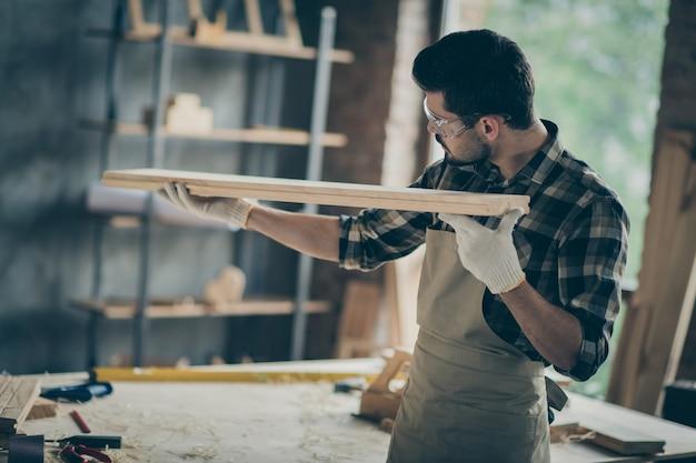 Vista traseira lateral traseira focada trabalhador homem segura placa de madeira lisa teste móveis reparados à mão na garagem de casa