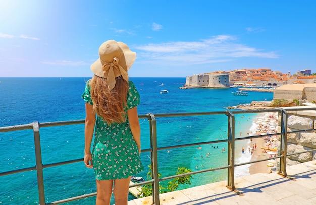 Vista traseira linda garota olhando para a cidade velha de dubrovnik, na croácia, europa. férias de verão no mar mediterrâneo.