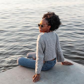 Vista traseira linda mulher sentada ao lado da água