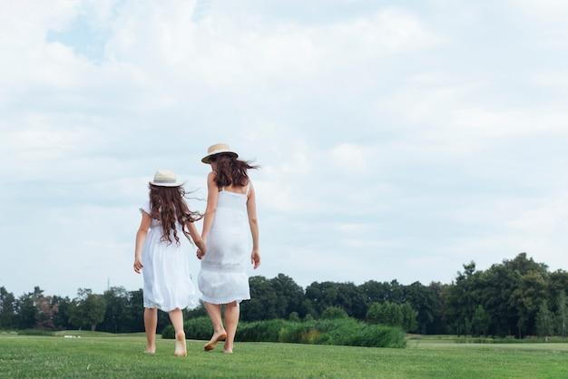 Vista traseira, mãe filha, andar, ao ar livre