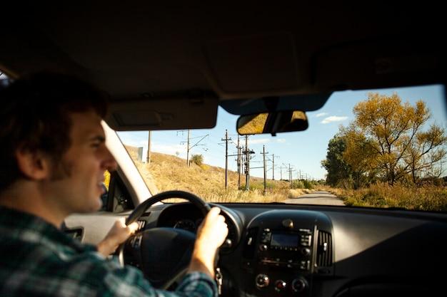 Vista traseira masculino motorista segurando o volante