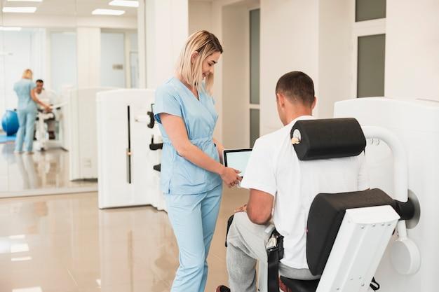Vista traseira médico ajudando paciente com um médico exercitado