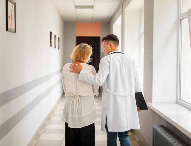 Vista traseira médico e mulher sênior andando