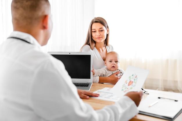 Vista traseira médico falando com a mãe de um bebê