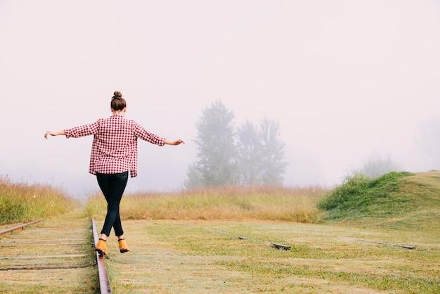 Vista traseira, menina adolescente, equilibrar, perto, estrada ferro