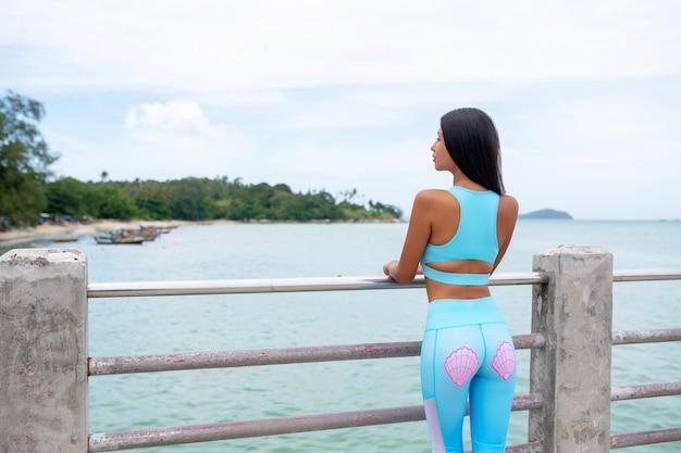 Vista traseira: menina bonita asiática no cais de madeira no mar em dia de verão. garota magra no sportswear posando perto do mar. moda e estilo . saque perfeito