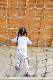 Vista traseira menina da criança no campo de jogos que joga na rede da corda de escalada.
