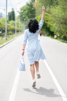 Vista traseira menina morena de vestido azul claro