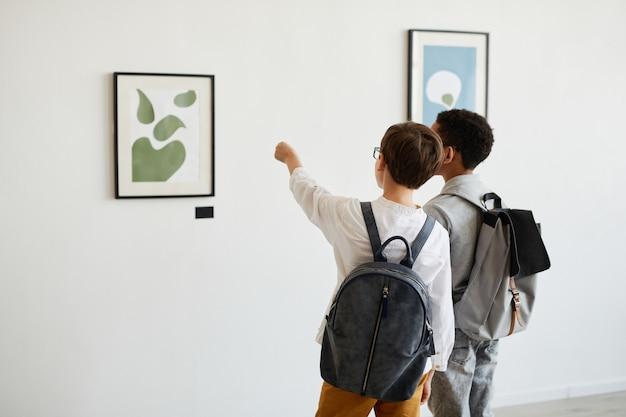 Vista traseira mínima de dois alunos olhando pinturas na galeria de arte moderna, copie o espaço