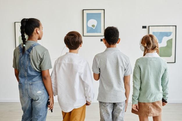 Vista traseira mínima de um grupo multiétnico de crianças olhando pinturas na galeria de arte moderna e usando fones de ouvido