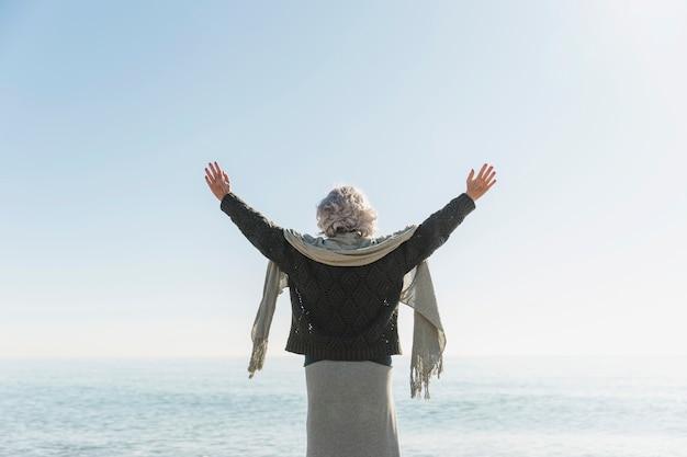 Vista traseira mulher à beira-mar