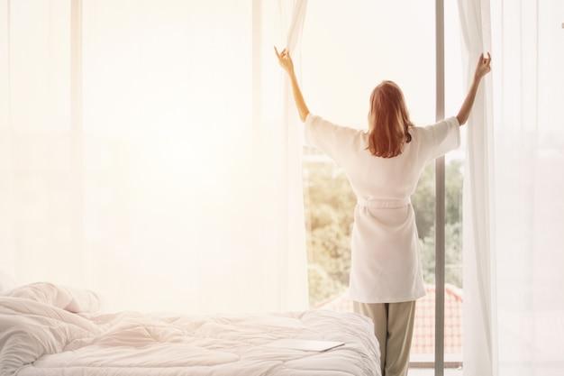 Vista traseira, mulher, abrindo cortinas, em, um, branca, quarto