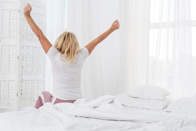 Vista traseira mulher acordando de manhã