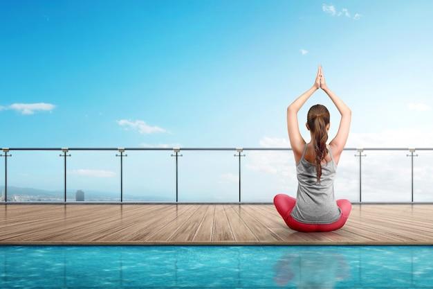 Vista traseira mulher asiática fazendo yoga no piso de madeira