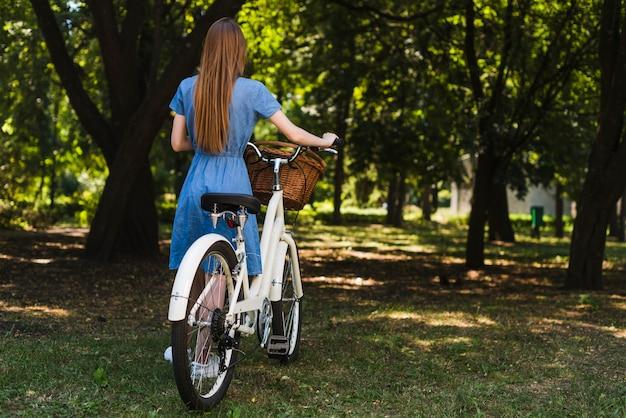 Vista traseira, mulher caminhando, perto, bicicleta