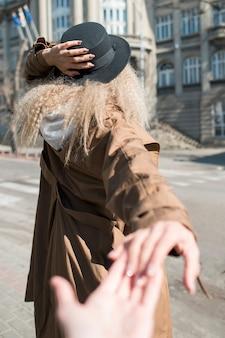 Vista traseira mulher com cabelos cacheados, segurando a mão do amigo