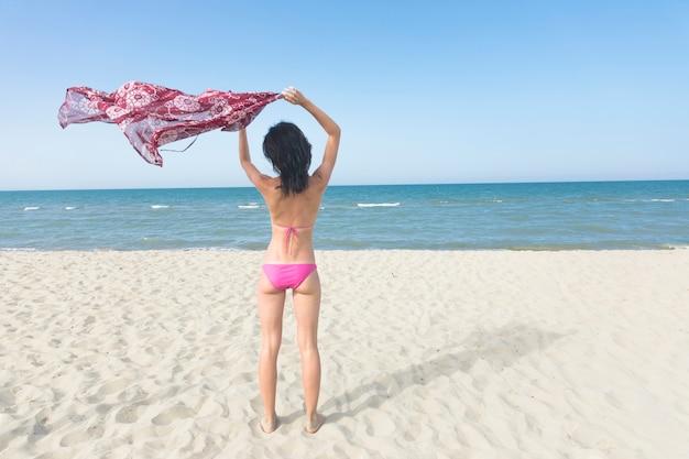 Vista traseira mulher em pé na praia olhando para o mar