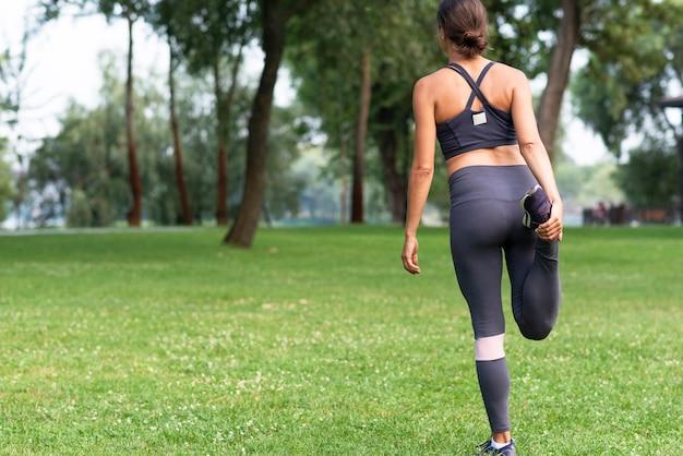 Vista traseira mulher esticando a perna