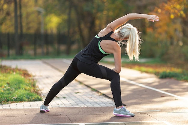 Vista traseira mulher fazendo exercícios de alongamento