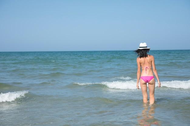 Vista traseira, mulher, ficar, em, água, em, praia