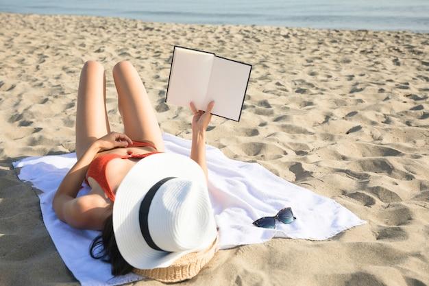 Vista traseira, mulher, ligado, praia, lendo um livro
