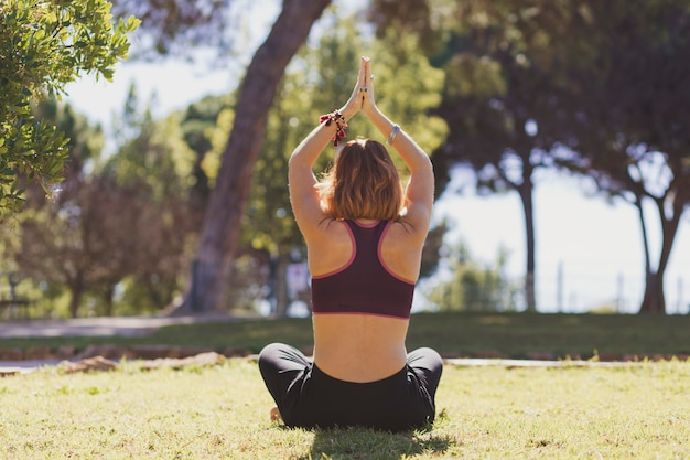 Vista traseira, mulher meditando, parque