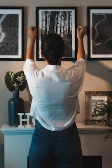 Vista traseira mulher organizando uma pintura