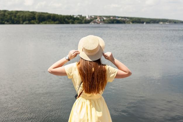 Vista traseira mulher perto do lago