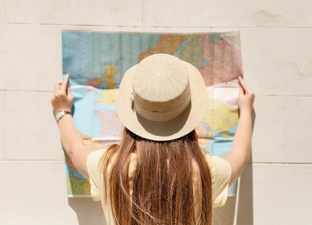 Vista traseira mulher segurando mapa