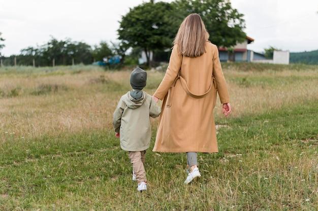 Vista traseira mulher segurando seu filho pela mão