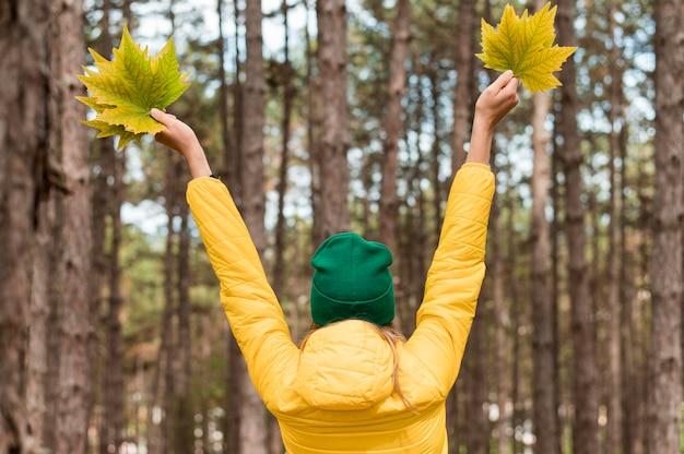 Vista traseira mulher sendo entusiasta sobre o outono