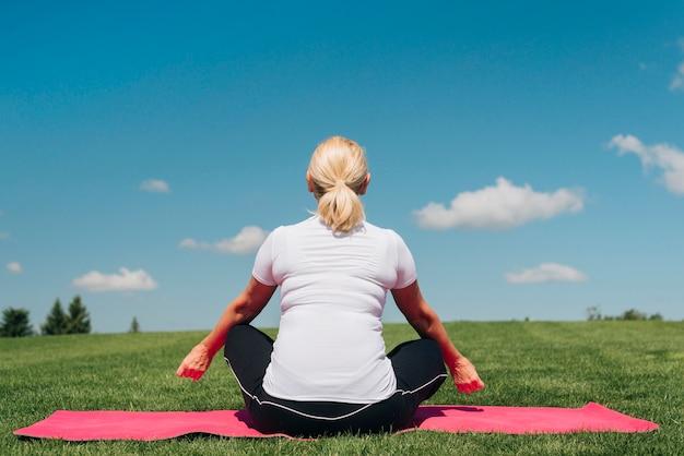 Vista traseira mulher sentada no tapete