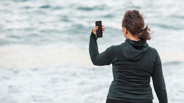 Vista traseira mulher tirando selfie
