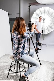 Vista traseira mulher tirando uma foto do modelo