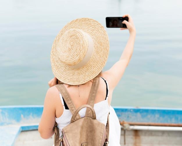 Vista traseira mulher tomando selfie