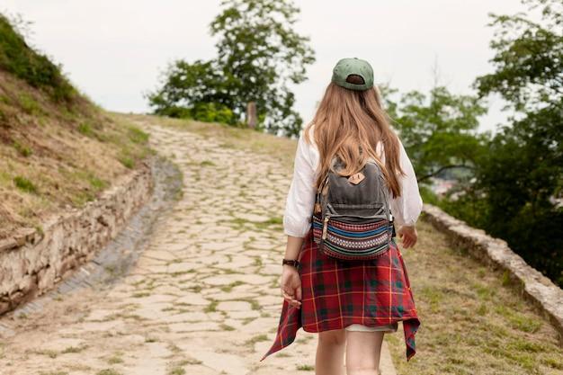 Vista traseira mulher usando mochila