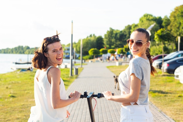 Vista traseira, mulheres, ligado, scooter, olhando câmera