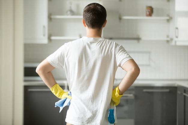 Vista traseira nas mãos do homem em seus quadris, observando cozinha