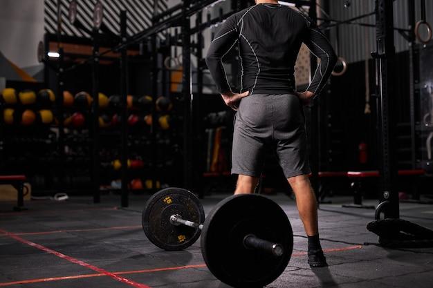 Vista traseira no desportista em pé perto da barra para fazer uma pausa, descanso. homem com roupa esportiva em academia moderna