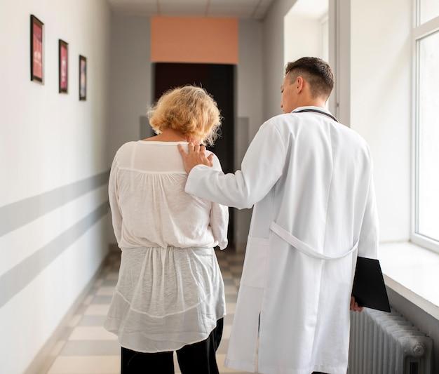 Vista traseira paciente sênior e médico andando