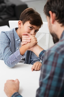 Vista traseira pai fazendo skandenberg com seu filho