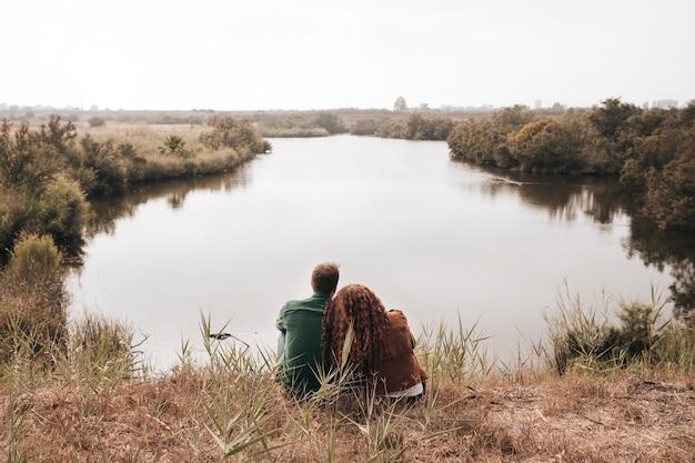 Vista traseira, par, sentando, perto, um, lagoa