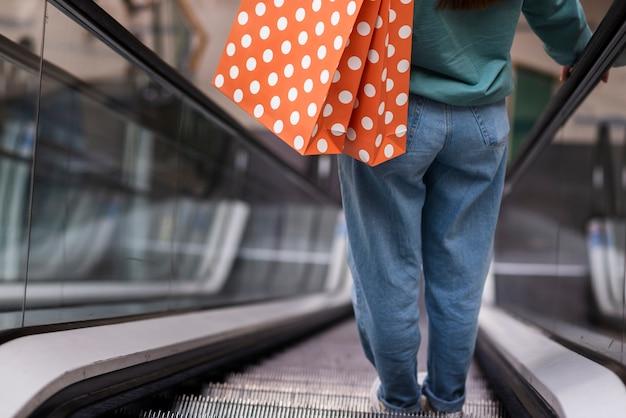 Vista traseira pessoa descendo escada rolante